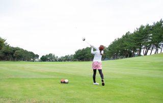 ゴルフのショットを打つ女性